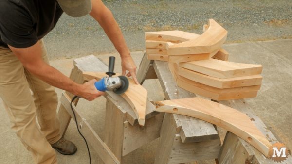 Stack of corner braces are chamfered with angle grinder and sanding disc attachment