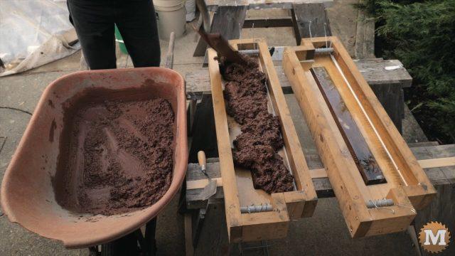shovelling wet perlite concrete into forms
