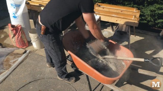 adding dry portland cement to the wheelbarrow to make the perlite concrete