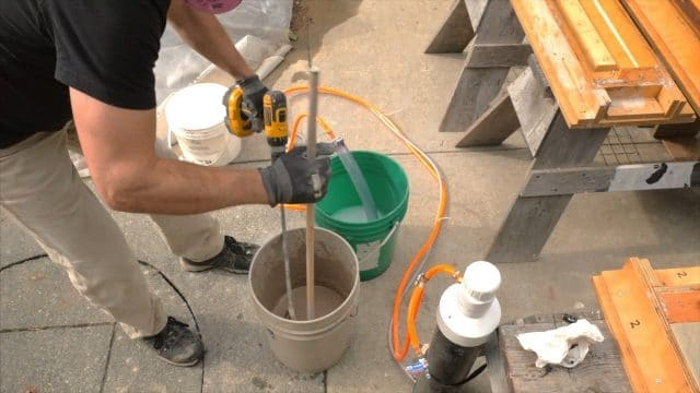 using a dowel to scrap mix off the side of the pail