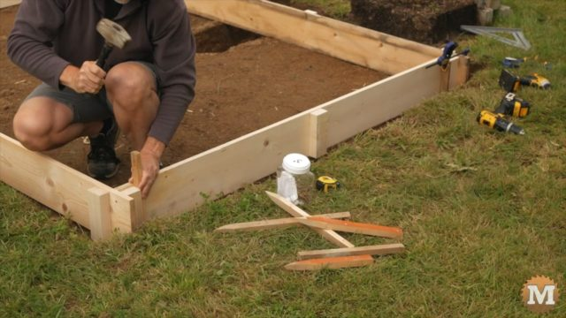 setting concrete forms in place and securing with stakes hammered into the ground