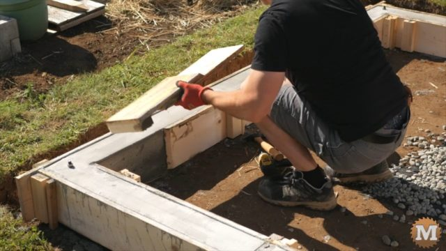 stripping the concrete form from the poured base curb walls