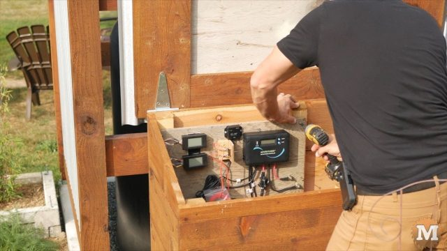 attaching board to wall of mini off grid pump house